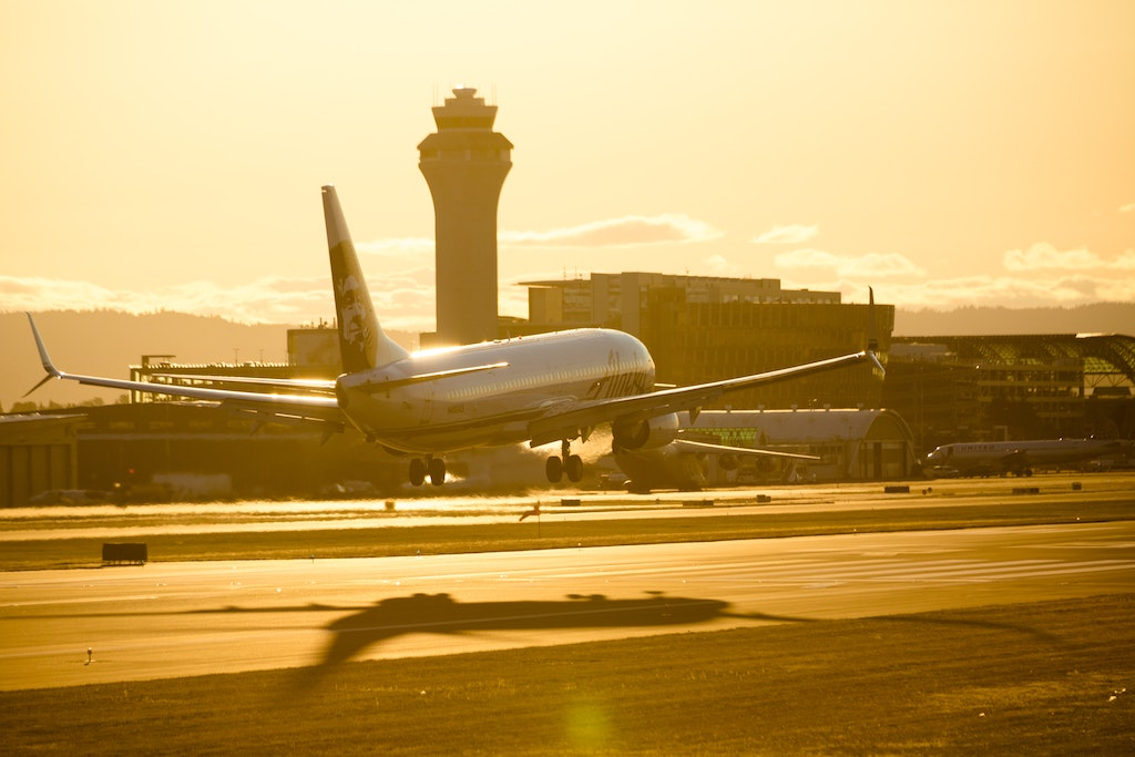 Photo of a passenger plane landing at an airport in the sunset